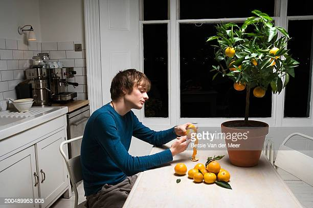 Young man peeling oranges picked from potted tree on kitchen table