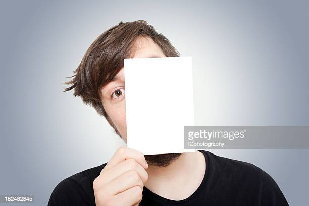 young man peeping from behind a piece of paper - greeting card bildbanksfoton och bilder