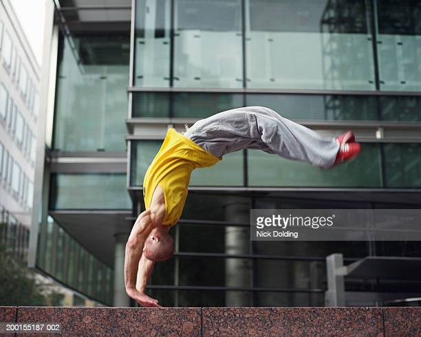 Young man performing backflip on wall outdoors (blurred motion)
