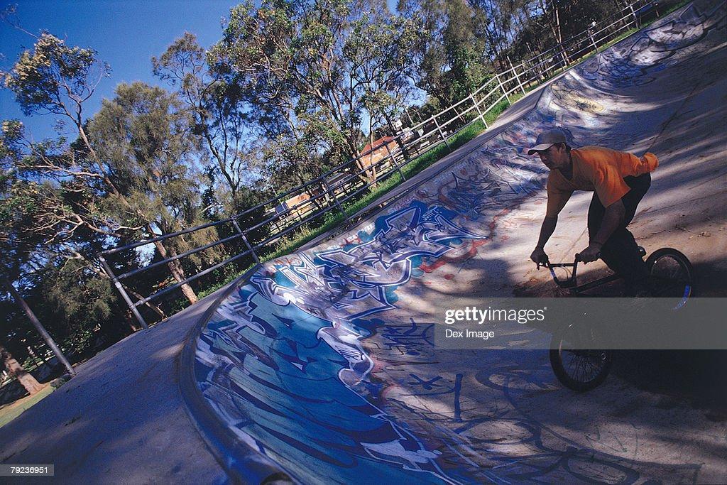 Young man performing bike stunt on ramp : Stock Photo