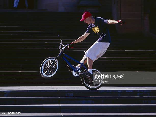 Young man performing bike stunt on stairs
