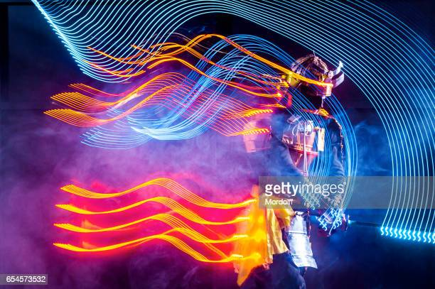 young man performing dance with led glow katana - warrior person stock photos and pictures