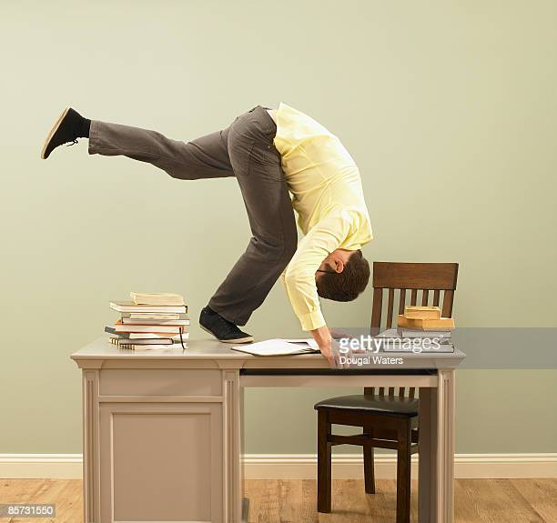 young man performing forward roll on desk. - somersault stock pictures, royalty-free photos & images