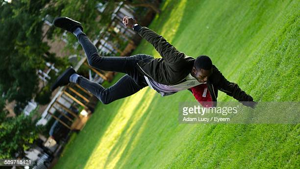 Young Man Performing Handstand On Grassy Field In Playground