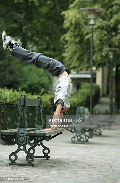 Young man performing handstand on park bench, side view