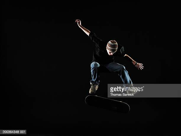 Young man performing jump on skateboard