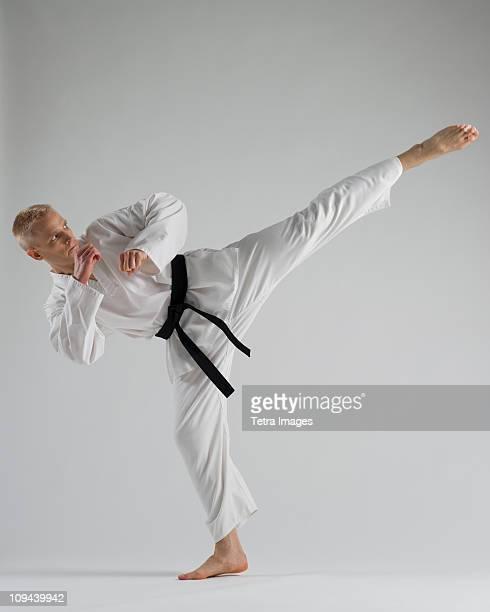 young man performing karate kick on white background - donner un coup de pied photos et images de collection