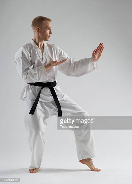 Young man performing karate stance on white background