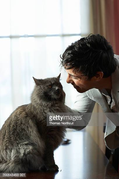 Young man petting cat, side view