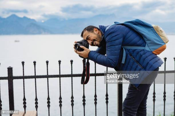 Young man photographer shooting on location with backpack
