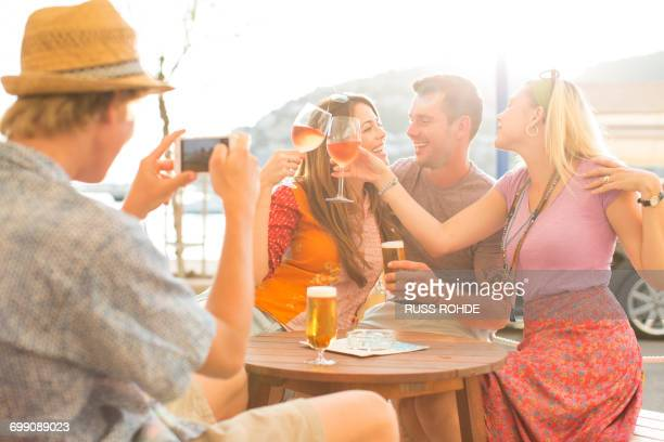 Young man photographing adult friends at waterfront restaurant, Majorca, Spain