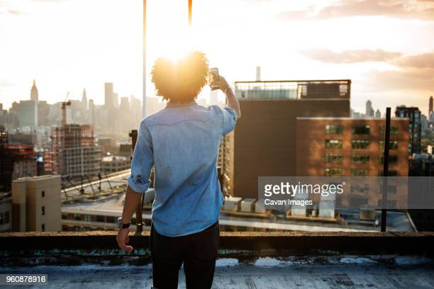 Young man photographing city against sky during sunset