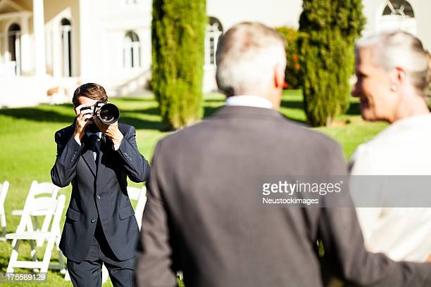 Young Man Photographing Couple At Outdoor Wedding