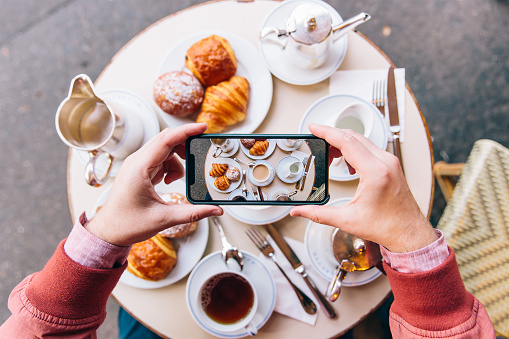 Young man photographing French breakfast with croissants on the table in sidewalk cafe with smartphone, Paris, France - gettyimageskorea