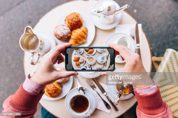 young man photographing french breakfast with croissants on the table in sidewalk cafe with smartphone, paris, france - food photos et images de collection