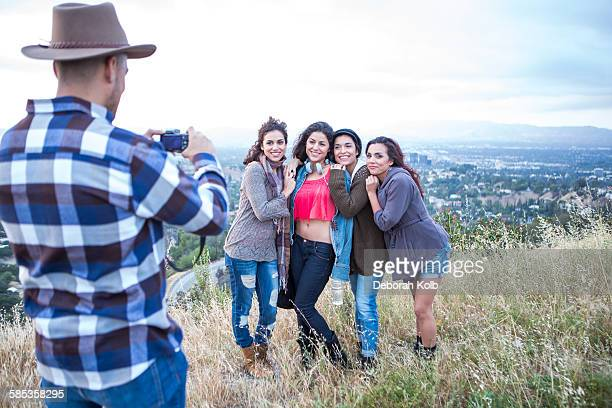 Young man photographing his four adult sisters on rural hill