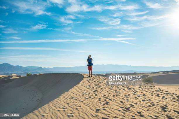 Young man photographing sand dunes, tourist, Mesquite Flat Sand Dunes, foothills of Amargosa Range behind, Death Valley, Death Valley National Park, California, USA