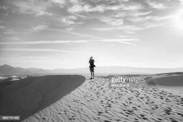 Young man photographing sand dunes, tourist, Mesquite Flat Sand Dunes, Amargosa Range behind, Death Valley, Death Valley National Park, California, USA