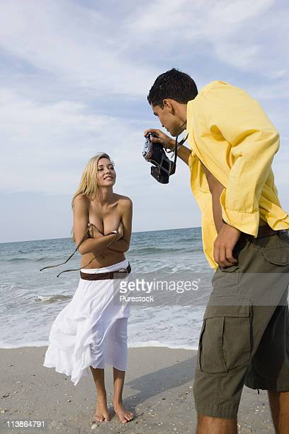 young man photographing scantily clad woman on the beach - scantily clad women stock photos and pictures