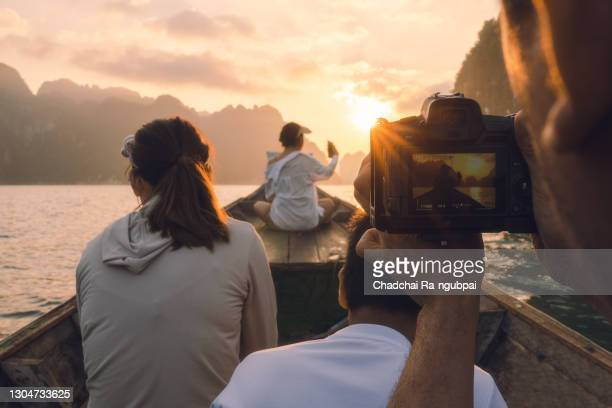 young man photographing sunset while sailing on a long-tail boat in thailand - majestic stock pictures, royalty-free photos & images