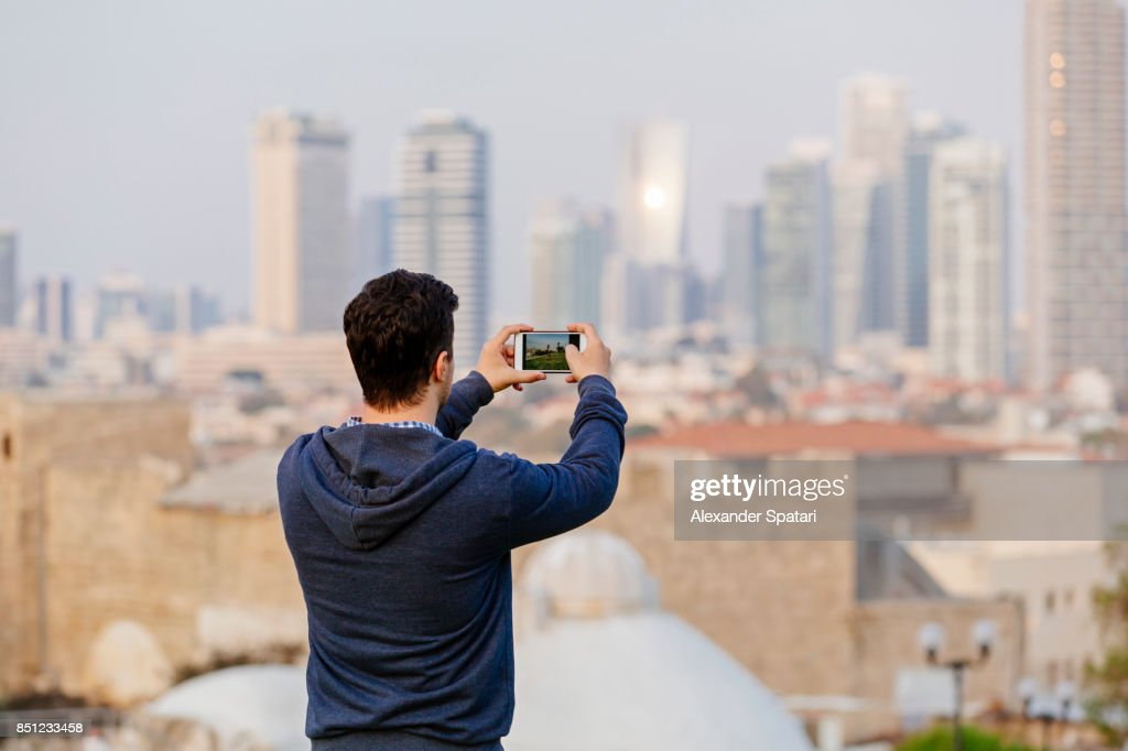 Young man photographing Tel Aviv skyline, Israel : Stock Photo