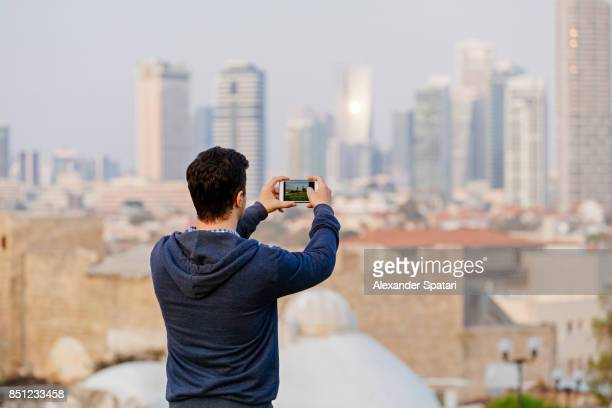 Young man photographing Tel Aviv skyline, Israel