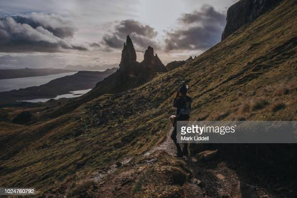 young man photographing the old man of storr, overlooking loch leathan and sound of raasay, isle of skye - ridge stock pictures, royalty-free photos & images
