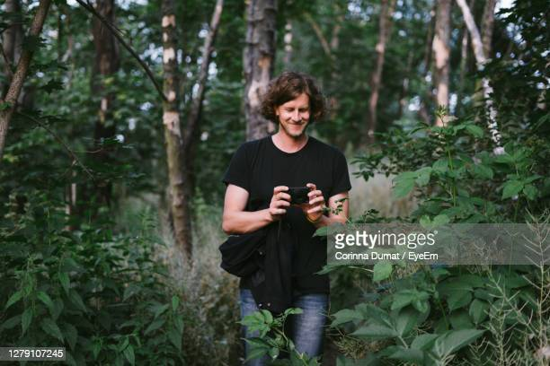young man photographing through camera in forest - photographer stock pictures, royalty-free photos & images