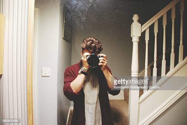 Young Man Photographing With Camera At Home