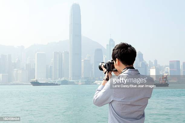 young man photographing with slr camera in victoria harbor, hong kong - star ferry stock photos and pictures