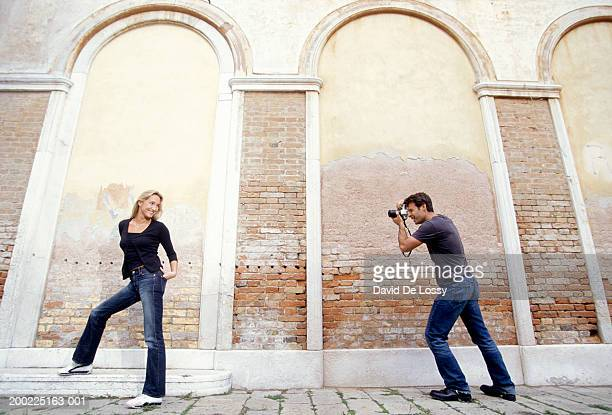 Young man photographing young woman, posing at brick wall