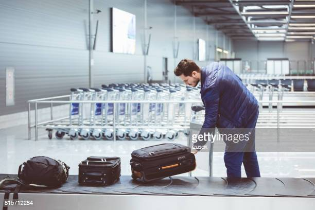 young man picking luggage from conveyor belt in airport - baggage claim stock pictures, royalty-free photos & images