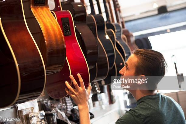 Young man picking out guitar in shop