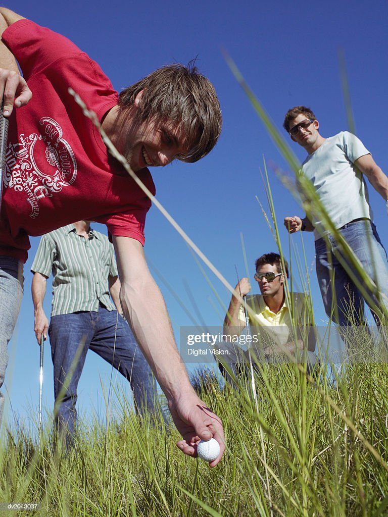 Young Man Picking Up a Golf Ball From Grass : Stock Photo