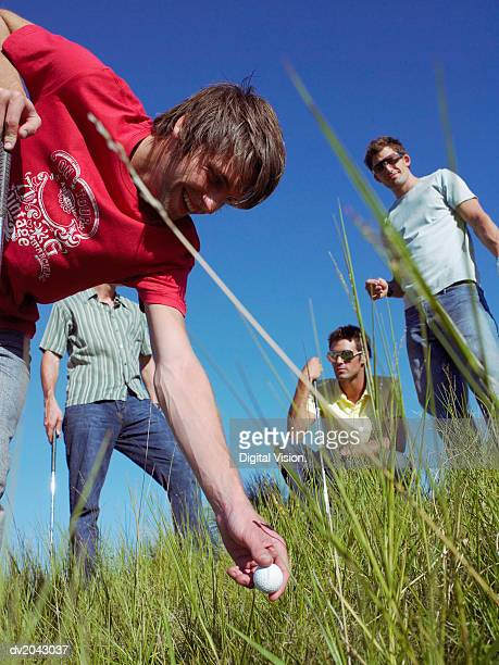 young man picking up a golf ball from grass - amateur stock pictures, royalty-free photos & images
