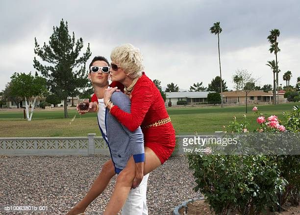 young man piggybacking senior woman holding wine glass, side view - may december romance stock photos and pictures