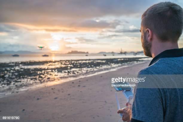 若い男が日没で熱帯のビーチに無人機を操縦