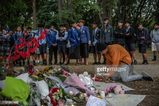 A young man places a candle among flowers and tributes during a students vigil near Al Noor mosque on March 18 2019 in Christchurch New Zealand 50...