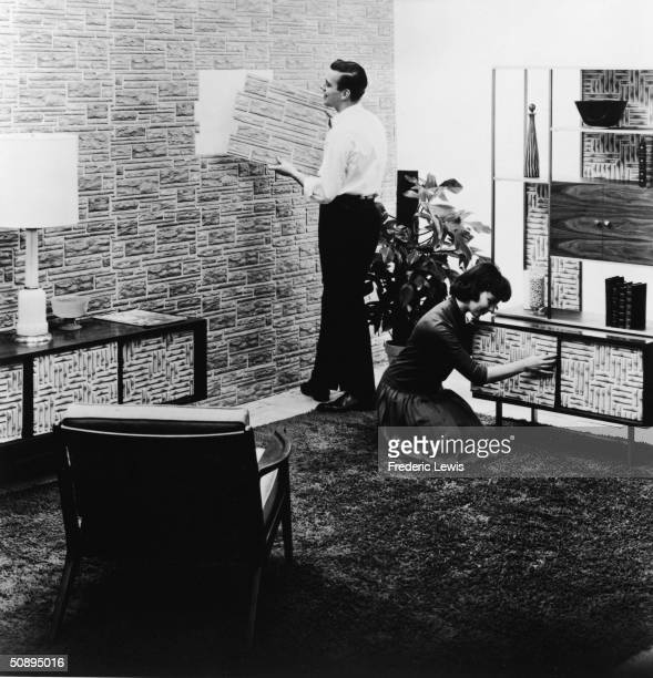 A young man places fake stone panelling on the wall as a kneeling young woman applies fake bamboo panelling to furniture in their living room laid...