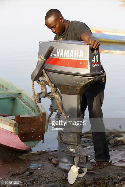 Young man placing an engine on a boat Ziguinchor Senegal