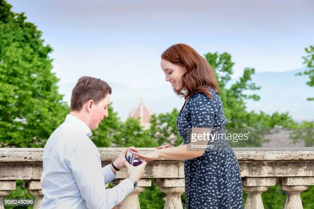 Young man placing engagement ring on woman's finger, Florence, Toscana, Italy