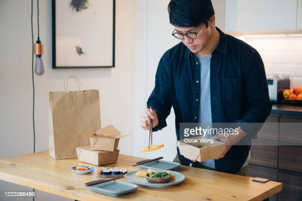 young man placing takeaway food on plate - take away food stock pictures, royalty-free photos & images