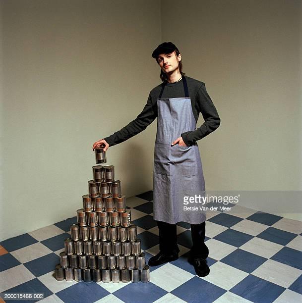 Young man placing tin can on top of tin can pyramid