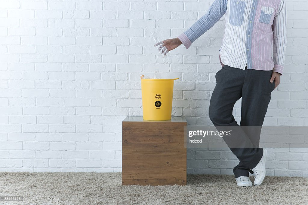 Young man placing water bottle to trash can : Stock Photo