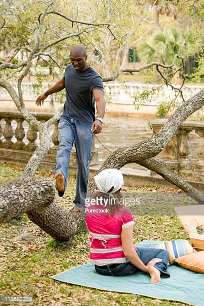 Young man playfully walking on tree branch with girlfriend watching