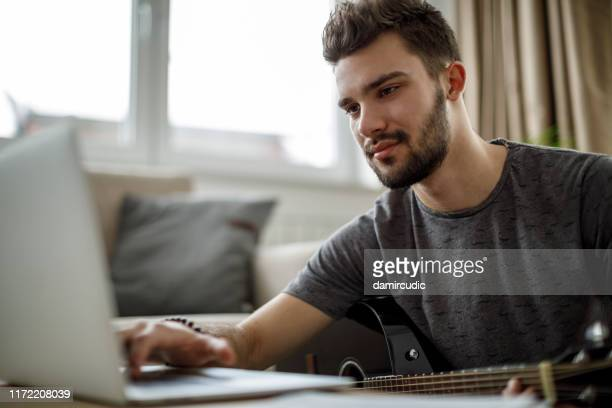 young man playing a guitar at home - tutorial stock pictures, royalty-free photos & images
