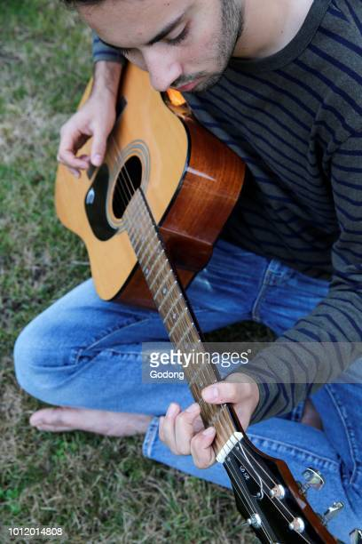Young man playing a guitar in a garden France