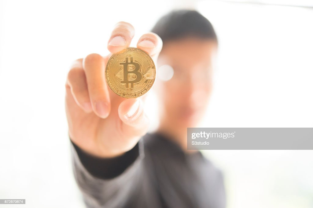 Young man playing a visual representation of the digital Cryptocurrency, Bitcoin with US Dollar on November 9, 2017 in Hong Kong, Hong Kong. Cryptocurrencies - Bitcoin, have seen unprecedented growth in 2017.