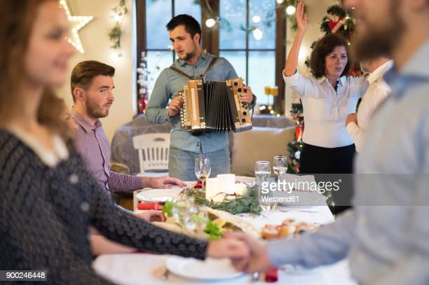 young man playing accordion for family at christmas - accordionist stock pictures, royalty-free photos & images