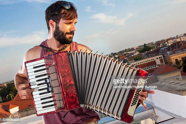 Young man playing accordion on roof terrace
